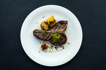american rib steak on dark background. Barbecued and seasoned delicious quality meat dish.