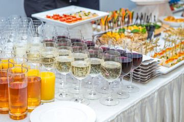 Catering table with alcoholic and non-alcoholic drinks, dishes and snacks food on the event. Service at business meeting, party, weddings. Selective focus, space for text.