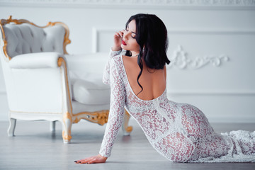 Perfect, sexy legs and ass of young woman wearing seductive white dress posing near luxury vintage chair