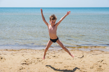 Six-year-old boy in black speedo jumping into the sea and smiles.