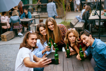 Group Of Friends Drinking Beer And Taking Photos On Phone