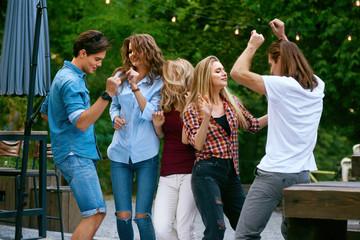 Happy Friends Dancing, Having Fun And Enjoying Party Outdoors.