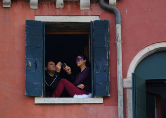 A man takes a picture from a window during the masquerade parade on the Grand Canal during the Carnival in Venice