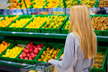 Consumerism concept. Woman doing grocery shopping at supermarket