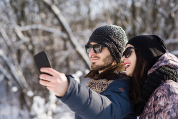 Smiling couple making selfie in winter outdoors