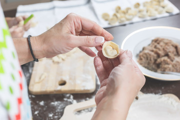 Female hands hold freshly dumplings on the background of kitchen workspace