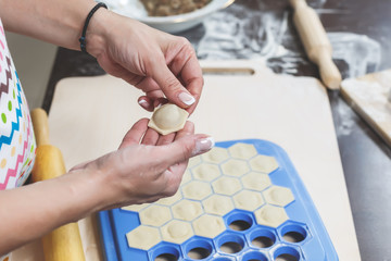 The process of making delicious homemade dumplings. Female hands hold freshly dumplings on the background of kitchen workspace