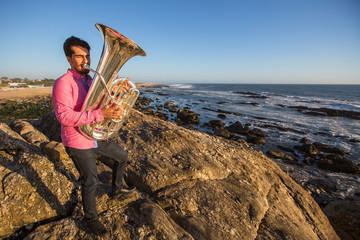 Musician play to Tuba on romantic ocean shore.