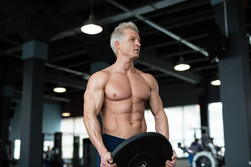 Strong man with muscular body working out in gym. Weight exercise with barbell in fitness club.