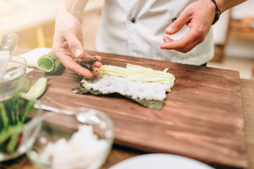 Male cook making sushi on wooden table, seafood