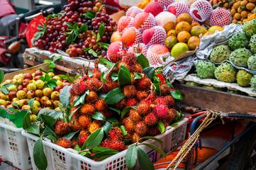 Exotic Asian fruit on local market. Asian cuisine concept.Fresh rambutans,Kiwano melon,kepundung, lemon