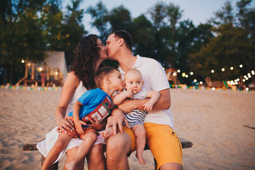 The concept of a family vacation. Young family sitting on a bench in the evening on a sandy beach. Mom and Dad kiss, the older brother kisses the younger on the cheek.