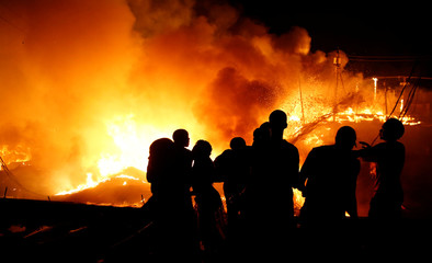 Residents pour water as they attempt to extinguish a fire that broke out at the Kijiji slum in Southlands estate of Nairobi