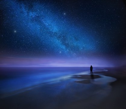 Starry night sky over sea and beach with man silhouette