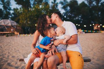 The concept of a family vacation. Young family and two sons sitting on a bench in the evening on a sandy beach. Mom and Dad kiss, the older brother kisses the younger on the lips