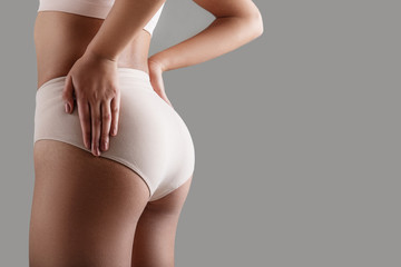 Close up of good looking female buttocks wearing high-waist panties. Copy space on right side. Isolated on background