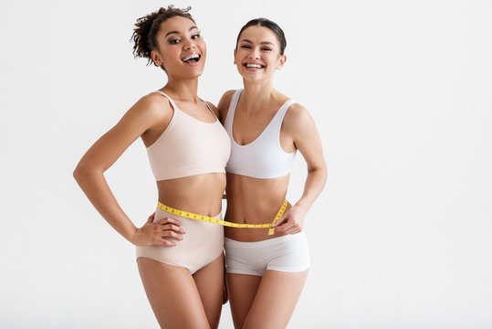 Skinny women leading healthy way of life. They are boasting about their body parameters and laughing. Copy space in right side. Isolated on background