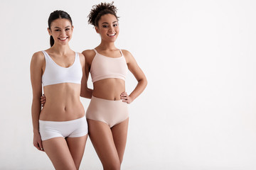 Portrait of two smiling women in great shape wearing tight underwear. They are hugging and looking at camera with joy. Copy space in right side. Isolated on background