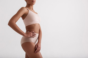 Serene woman leading healthy way of life. Her athletic figure is in high waist panties and brassiere. Copy space in right side. Isolated on background
