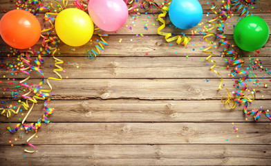 Colorful carnival or party frame of balloons, streamers and confetti on rustic wooden board