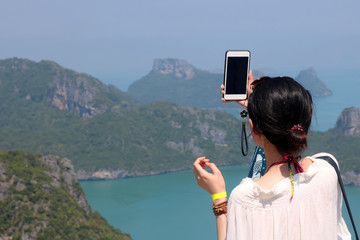 Asian girl selfie with smart phone on the top of mountain, Sea and island views