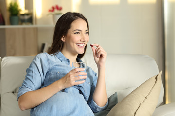 Happy pregnant woman taking a pill at home