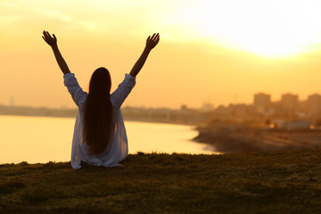 Happy woman seeing city at sunset and raising arms