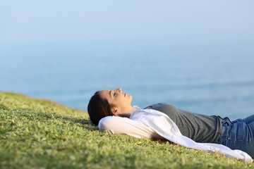 Relaxed woman resting on the grass in the coast