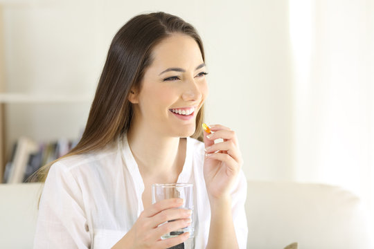 Happy woman taking a vitamin yellow pill at home