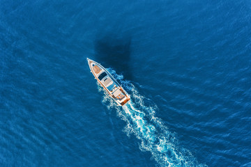Yacht at the sea in Europe. Aerial view of luxury floating ship at sunset. Colorful landscape with boat in marina bay, blue sea. Top view from drone of yacht. Luxury cruise. Seascape with motorboat