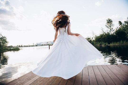 Redhead bride in a beautiful wedding dress on a wooden bridge on a lake