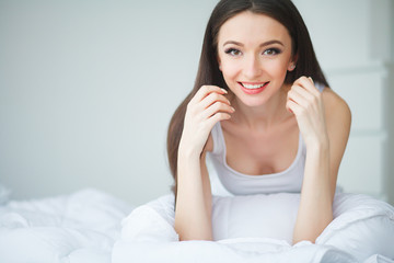 Selective focus on the beautiful dark-haired smiling girl wearing white pajamas lying in the bed looking at us thinking about miracle evening. Top view