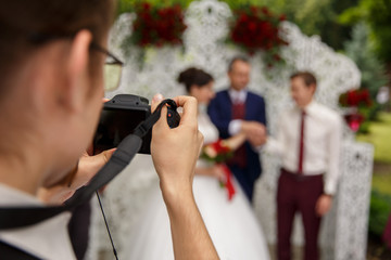 Man making promo videoblog or photo session on wedding. Vlogger promotion selfie solution, blogger recording video with camera at wedding ceremony. Bride, groom and priest near wedding arch