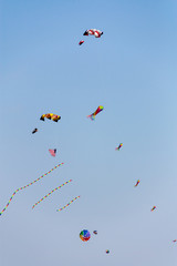 Colorful kites flying in the sky against a blue sky