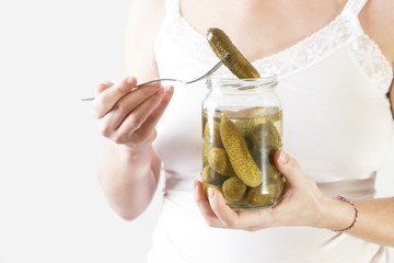 Pregnant woman holding jar of pickles - pregnancy food craving concept