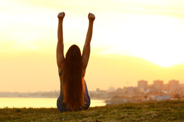 Excited woman raising arms watching the sunset on the city