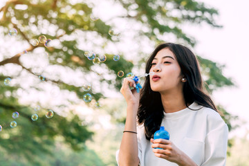 Beautiful woman blowing soap bubbles at summer green park