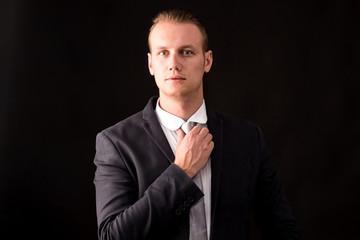 Portrait of handsome businessman on dark background