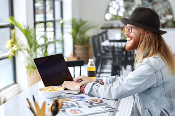 Positive glad hipster male has ginger thick beard, dressed in fashionable clothes, keyboards on laptop computer, creats new designed page for his magazine. Talanted professional journalist works