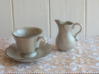 Tea set is Gray on a wooden background. Teapot, creamer, Cup and saucer on the table. Ceramic kitchenware