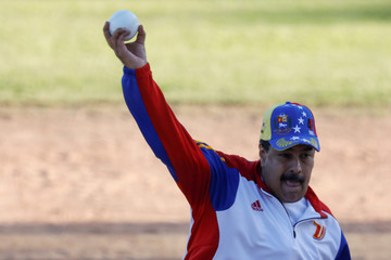 Venezuela's President Nicolas Maduro throws the ball during a softball game with ministers and military high command members at Fuerte Tiuna military base, in Caracas