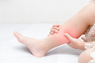 Leg pain or calf muscle in a girl on bed,