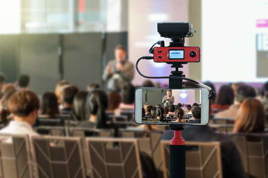Closeup smart mobile phone taking Live over Speakers on the stage with Rear view of Audience in the conference hall or seminar meeting, technology live streaming and broadcast concept