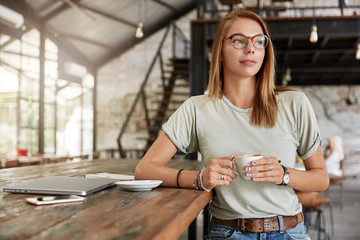 Beautiful woman wears spectacles and casual clothes holds mug with coffee, sits against cafe interior with laptop, smartphone and diary on wooden table, thinks about something. People and rest