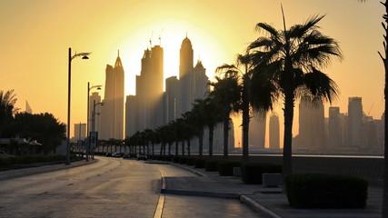 the skyline of Dubai marina from the artificial Palm Jumeirah island under the sunrise