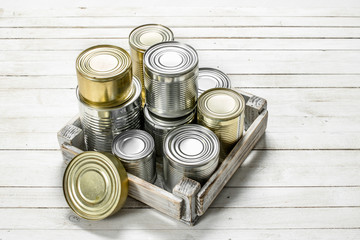 Tin cans with food in a box.