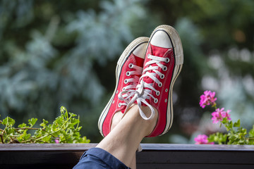 Red sneakers on the legs of a woman against the background of nature