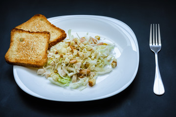 Salad of cabbage and beans and fried croutons on a white plate