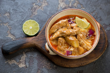 Bowl with massaman curry on a rustic wooden serving board, brown stone background, studio shot