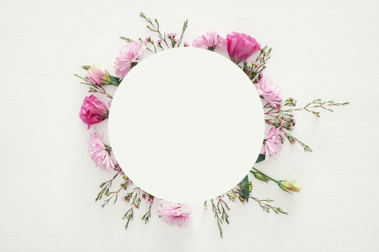 Top view of beautiful flowers arrangement on white wooden background. Copy space.